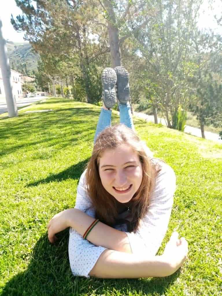 Mädchen liegt im Gras.
