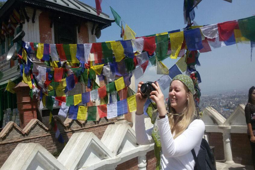 Nina fotografiert zwischen bunten Gebetsfahnen auf den Dachterrassen von Kathmandu